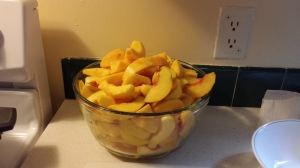 Two big bowls of peeled and sliced peaches are needed for a full canner load of 7 quarts